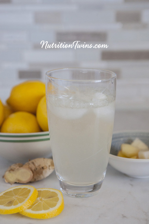 Glass of Pineapple Ginger Lemon DIY Soda with bowl of lemons, bowl of pineapple cubes, lemon slices and ginger root