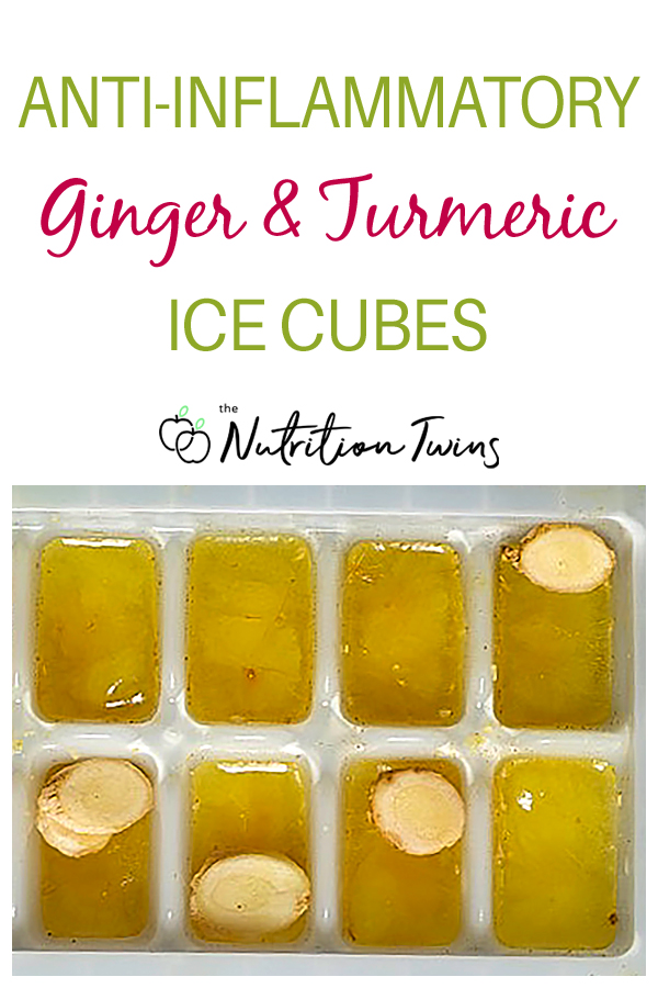 ginger turmeric ice cubes in tray with ginger slices